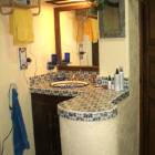 Spacious Bathroom with Make up Bar - the Bath has a Garden/Tub Shower with Mexican Tile Countertops in Yellows and Blues