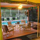 From Dining Area Looking Thru Opened Glass Wall to Florida Room to Pool to Backyard