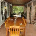 Covered Veranda with 8 Person Dining Table and Comfortable Patio Furniture.