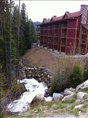 Backend Overlooks Keromeos Creek and Pine Forest.  - our Unit is in the Center of the Complex and Occupies the Bottom Two Floors. the Hot Tub is on the Lower Level Walk-out Patio.  There is a Small Deck above with a Propane Grill. Photo Shows Keromeos Creek during the Run-off.