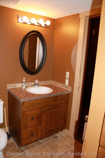 Main Bathroom is Spacious with a Tub, Sink, and Towel Storage.
