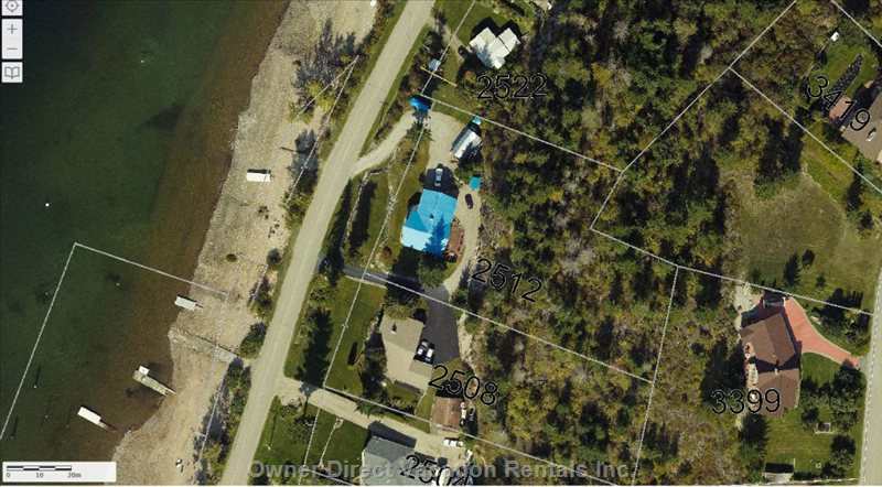 Aerial View of the Property the Blue Roof and Beach Front with Dock and Bouys