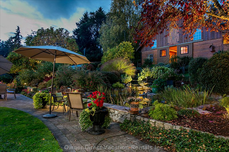 Another View of our Garden in the Evening, Overlooking the Pond and Waterfall with our Private Stable in the Background.