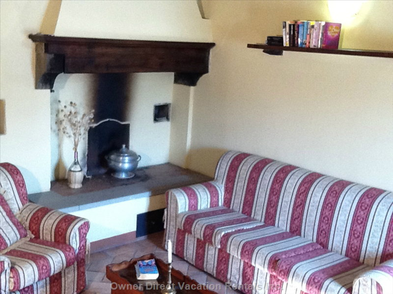 Sitting Room with Fireplace.  - the Sitting Room has a Comfortable Sofa and Two Comfy Armchairs Situated around the Wood Burning Fireplace. There is a TV, Books and Views from the Windows.
