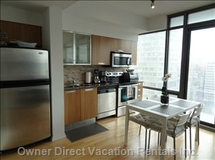 Modernized Kitchen with Stainless Steel Appliances and Dining Area.