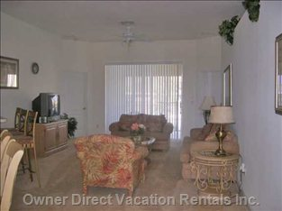 Large Family Room with TV and Patio Leading to Pool