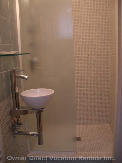 Mosaic Bathroom Featuring Large Shower, Designer Sink and Lighting and Towel Warmer.