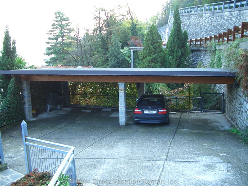 Carport with Car Parked in Owner's Single Spot.  Property is Entered through a Large Gate Using a Remote Control.