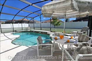 Oversize Pool Deck with Table and Chairs Taking in the Florida Sun all Day Long with a Glass of Wine by your Side.