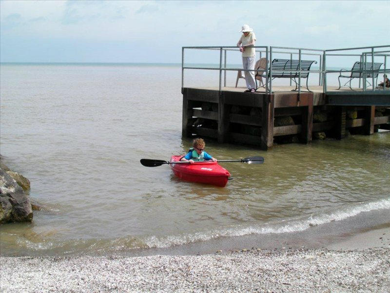 My Son Bringing his Kayak Back in to the Beach from Lake Erie as his Grandma Watches from the Fishing Pier.