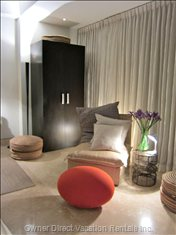 Romantic and Easy Seating Area Nesstled in  the Warmth of Shimmering Sheers Provide the Perfect Back Drop for Tv Viewing