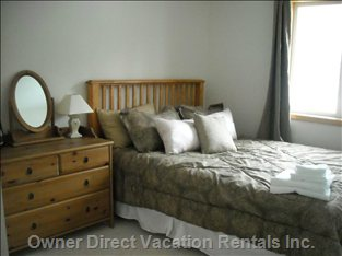Second Bedroom with Queen Sized Bed, Single Closet and Views of Castle Mountain.