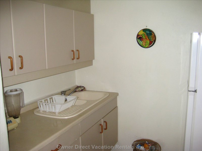 Cabinets and Kitchen Sink.   Fully Stocked with Dishes, Flatware, Glasses, Etc.