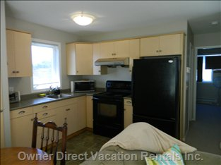 Kitchen with Full Size Stove & Fridge with Ice Maker.