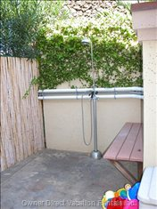 Variable Temperature Outdoor Shower by the Pool - an Assortment of Beach and Pool Toys for Small Children Provided