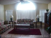 Living Room - has High Ceilings with a Ceiling Fan Comfortable Couches and a Beautiful Bay View.