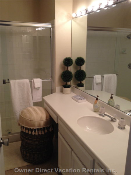 The Guest Room Bathroom has a Large Shower and a Long Makeup Counter with Adequate Lighting to Get Ready for the Day.