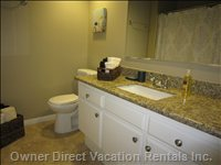 Bathroom with Granite Counters and a Shower over Tub