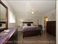 Master Bedroom with Queen Bed, 2 Dressers and Alarm Clock.  Easy Access to Washroom