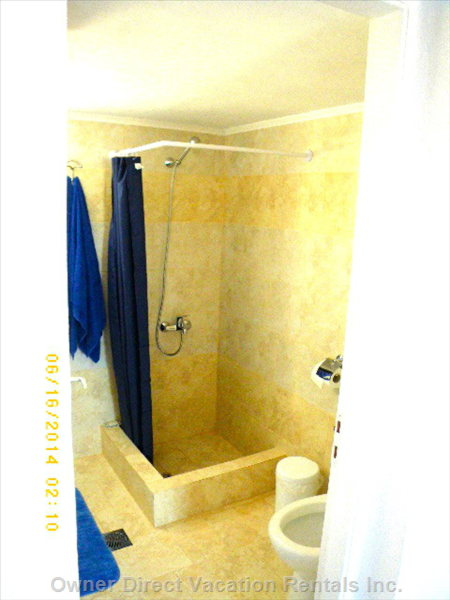 Bathroom with Shower, Sink, Toilet, and Washing Machine. Bathroom Also has a Window and Storage.