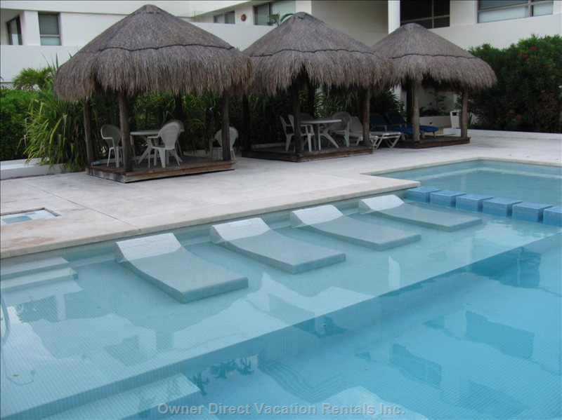 Large Pool with Shade Cabanas and Water Loungers.