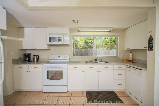 Well Equipped Kitchen with New Stove. Microwave Dishwasher and Sunny View to Back Garden