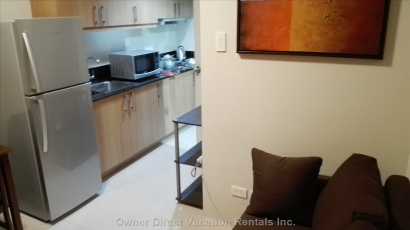 Kitchen with Stove, Large Refrigerator, 23l Digital Microwave, Rice Cooker, Electric Kettle, Silverware, Cookware, and Utensils.