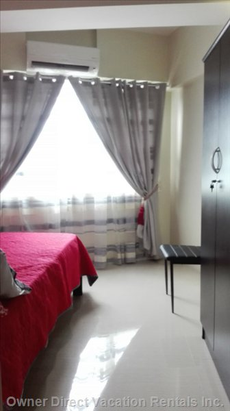 Entrance into the Bedroom with Double Drapes, Split Aircon Unit, Double Bed, Large Wardrobe.