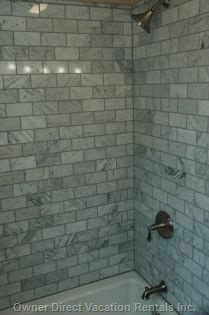 Shared Bathroom with Granite Tiled Shower.