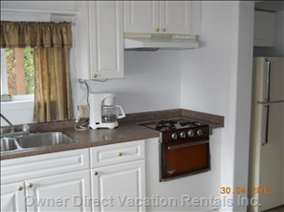 Close up of Kitchen Stove and Fridge.