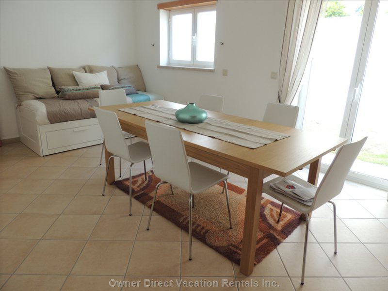 Dining Room with 6 Chairs, Can Accomodate 10. Daybed Opens into Double Bed. Patio Door Access to Side Rock Garden.