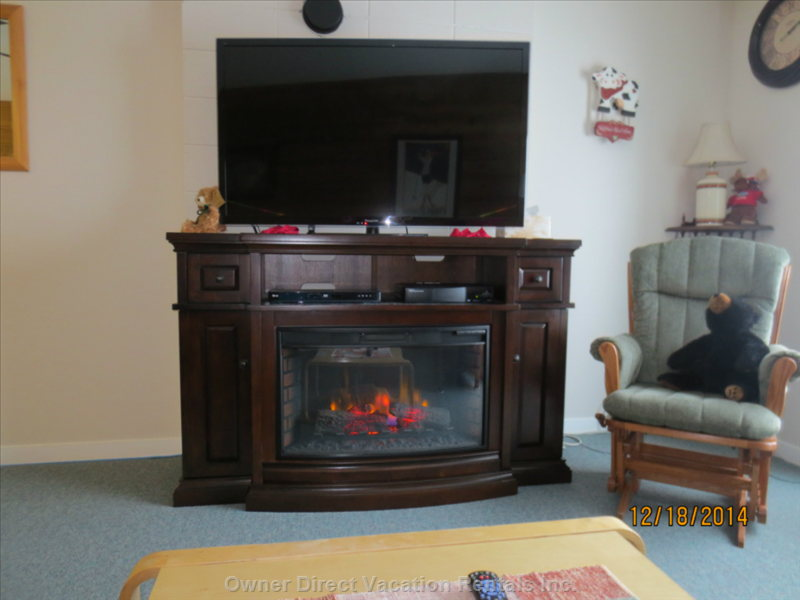 Large 55 Inch Smart Tv with a Cozy Electric Fireplace.