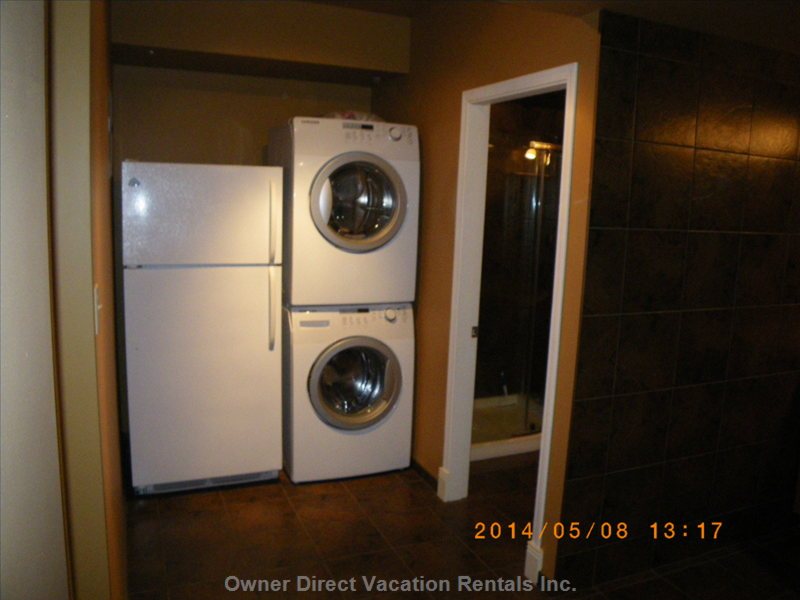 Fridge, Washer and Dryer on Back Wall of Kitchen Area. Doorway on the Right is the Washroom.