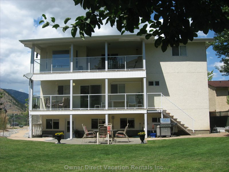 Back View Decks and Yard  - the Large Upper Deck is off the Upper Main Kitchen, the Long Main Floor Deck is off the Small Kitchen/Den.  this Lovely Green Large Backyard Faces South- with a Fabulous Bright Sunny Exposure.  the Decks, Secret Garden, and Large Trees Provide Easy Access to Cooler Temperatures and Shade.  Do Come for a Visit!