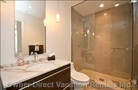 Rain Shower with Glass Enclosure and a Soak Tub with Marble Vanity and Heated Floors