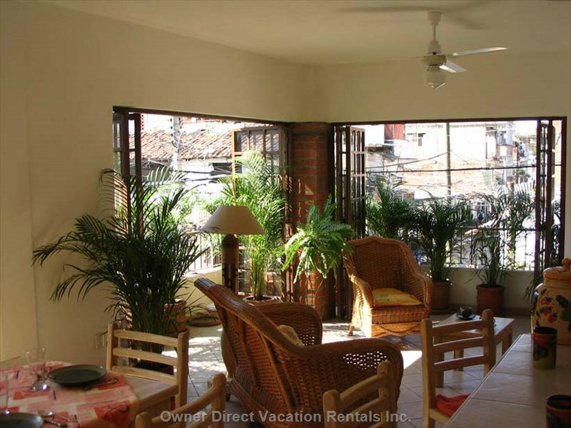 Living Area with Sliding Doors and Wrap around Balcony Filled with Plants Providing that Indoor/Outdoor Living Affect.