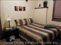 Lower Level Spacious Bedroom with En Suite has Queen Bed, Closet, Electric Fireplace Heater and Relaxing Decor