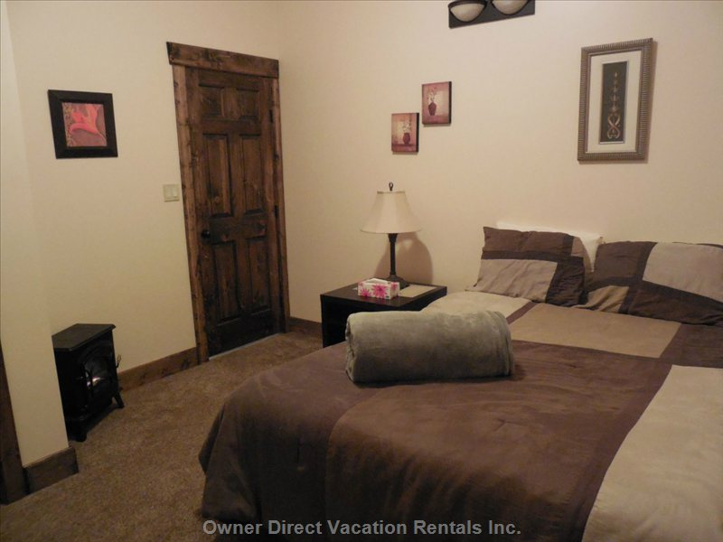 Large Lower Level Bedroom with Queen Bed, Closet, Electric Fireplace Heater in a Relaxing Decor for a Good Night's Rest
