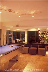 Pool Table Adjacent to Sunken Bar and Wine Cellar