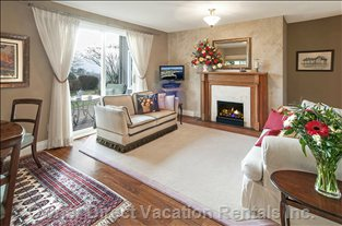 Living Room Showing Cosy Fireplace and Glass Doors Opening onto your Private and Generous Patio with Bbq