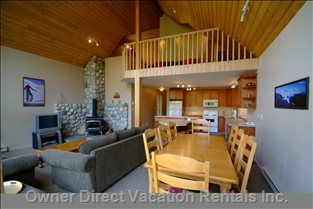 Living, Dining and Kitchen - True Ski Chalet with Open Living Room, Floor to Ceiling Glass View of the Ski Slope, and Quad Ski Lift Right Outside.