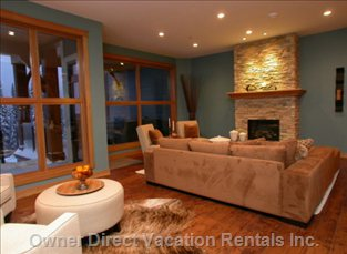 Living Room Features a Floor to Ceiling Rock Fireplace and Tall Corner Windows. A Perfect Place to Relax after a Day of Skiing