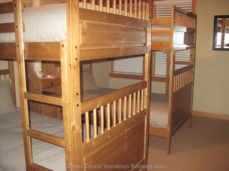 Third Bedroom - Two Sets of Bunk Beds - Sleeps 4. each Bed has a Feather Duvet and Feather Pillow. a Shelf Unit between the Beds Provides Lamps for Upper and Lower Bunks. the Closet has Beach Towels for the Pool as Well as Extra Storage.