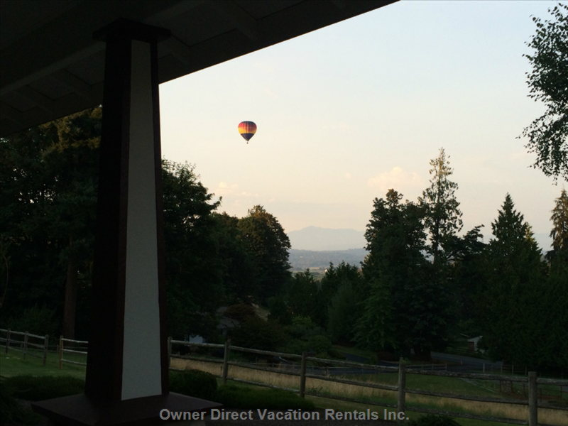 Hot Air Balloon Drifting by over the Valley.