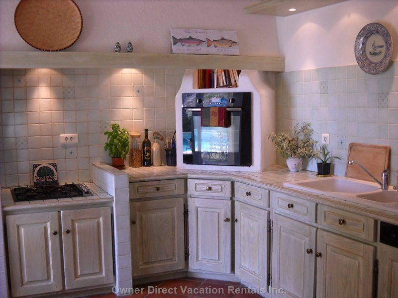 Kitchen - American Style, Open, with Modern Oven, Range and Dishwasher, Also a Kitchen Bar with Two Stools.