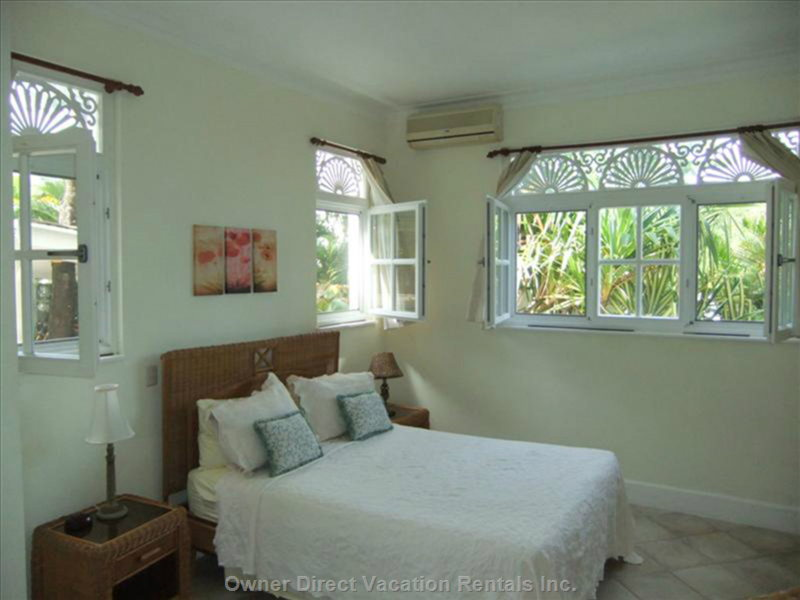 The Large Bedroom has a Queen Sized Bed and Plenty of Windows that Overlook the Grounds.