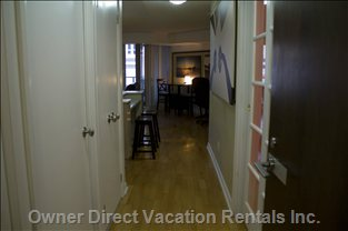 View from the Entrance of Unit - Washroom Door to the Left, Sliding Doors to the Den on the Right