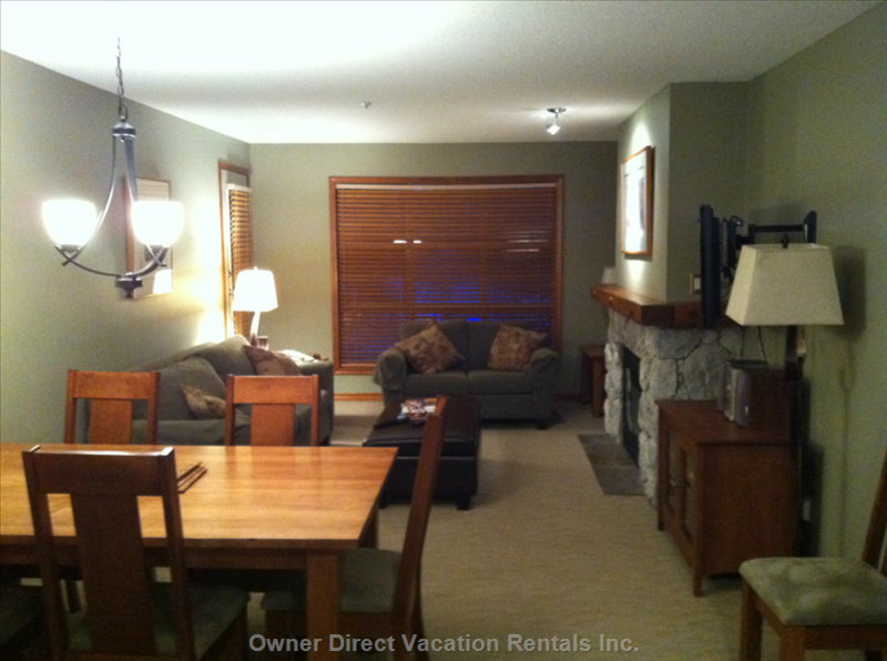 Dinning Area and Living Room with Queen Size Pull out Bed at the Left and a Gas Fireplace at the Right