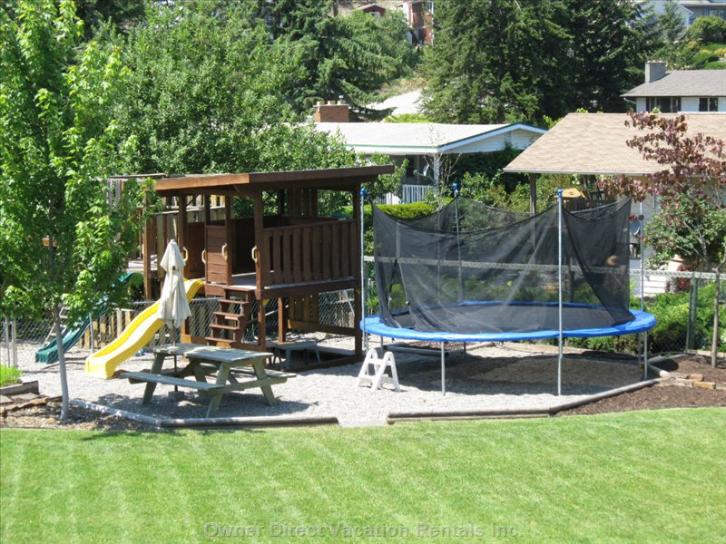 A Picnic Table, Play Structure and Trampoline Make a Great Play Area for the Kids.