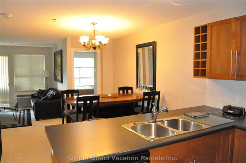 Large Spacious Counter Height Dining Table with Upholstered Tall Chairs.   Peninsula Island Kitchen has Barstools.
